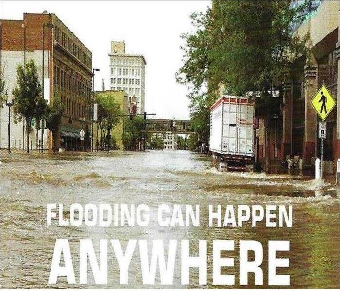 """Flooding Can Happen Anywhere"" caption in front of a flooded street"